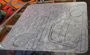 Back of a road sign with a polished silbver surface and some traced shapes ready to be cut out