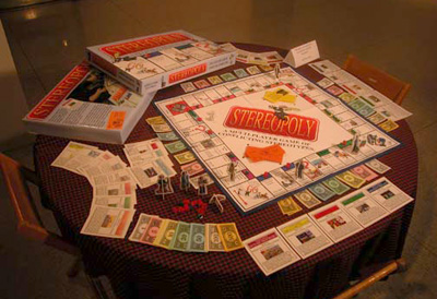 The stereoploy game is shown set up with the card, board, pieces, and box present on a table in the art gallery at Allegheny College